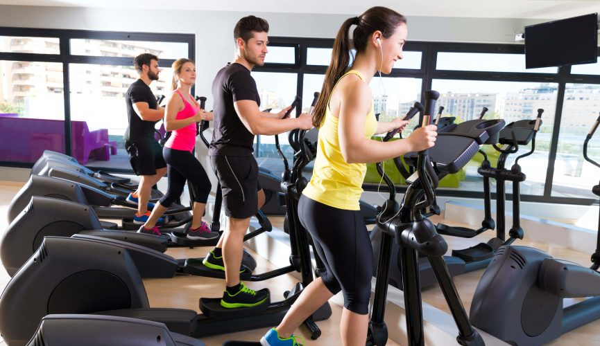 Group of people working out on elliptical trainers